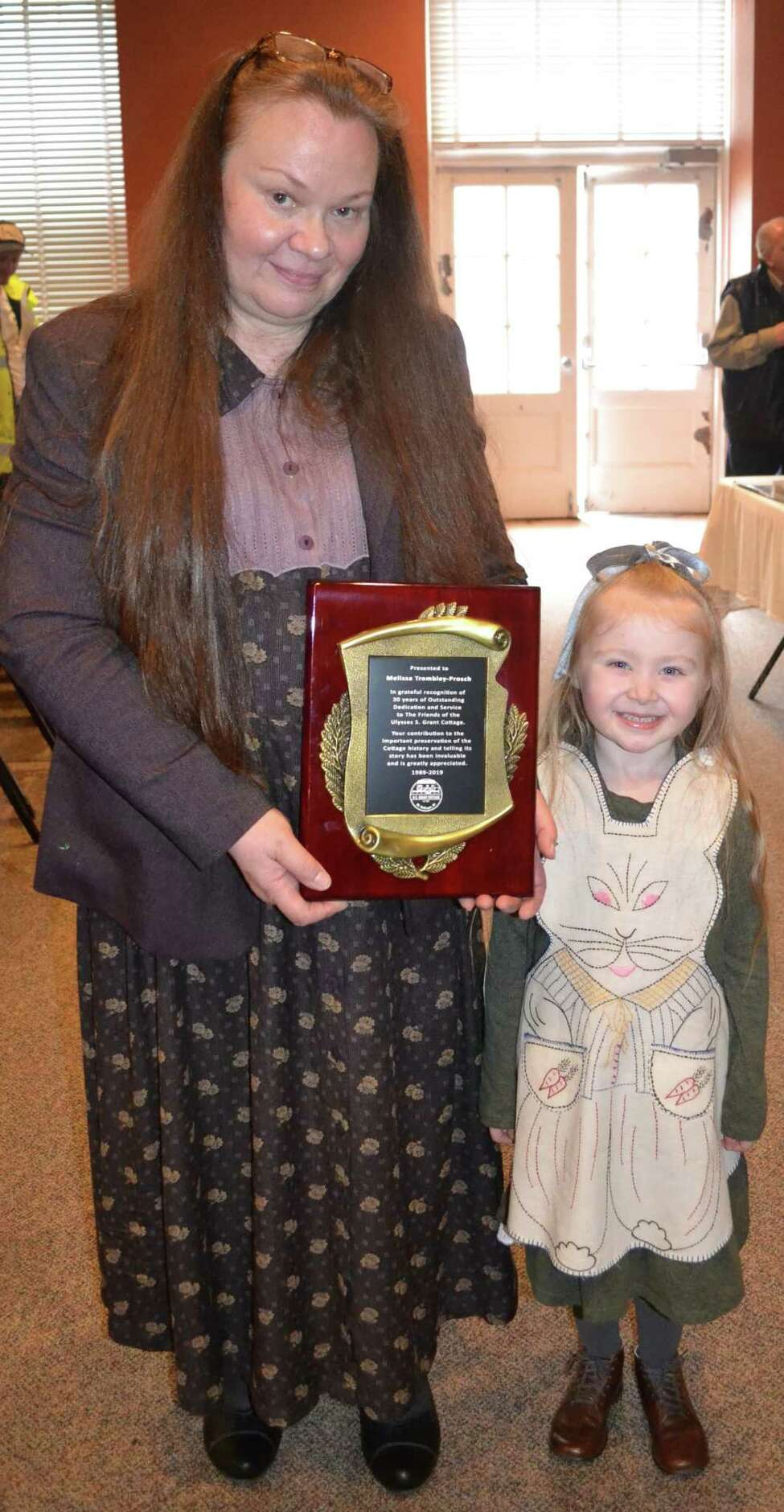 Melissa Trombley-Prosch, founding member of the Friends of Grant Cottage, is seen with her grandaughter, Delilah Robinson, as she was recognized for her long service to the nonprofit group. (Photo provided)