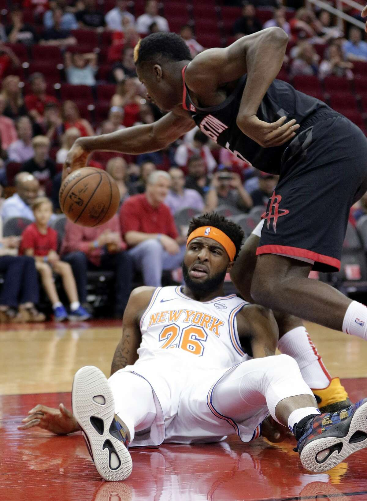 Houston Rockets center Clint Capela, top, chases the ball after New York Knicks center Mitchell Robinson (26) lost it on a fall during the first half of an NBA basketball game Friday, April 5, 2019, in Houston. (AP Photo/Michael Wyke)