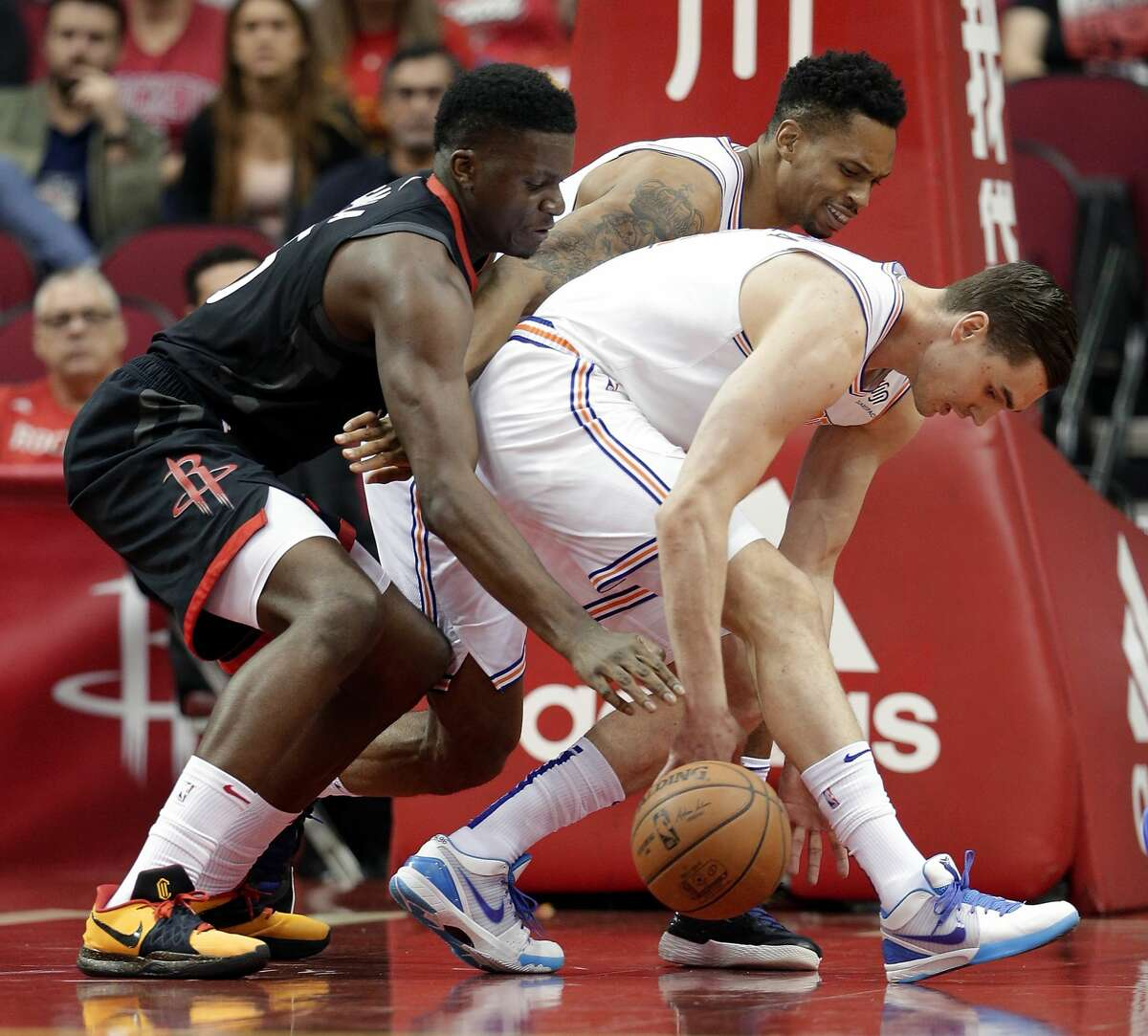 Houston Rockets center Clint Capela, left, reaches for the ball after knocking it away from New York Knicks forward Mario Hezonja, right, as forward Lance Thomas, back, watches during the first half of an NBA basketball game Friday, April 5, 2019, in Houston. (AP Photo/Michael Wyke)