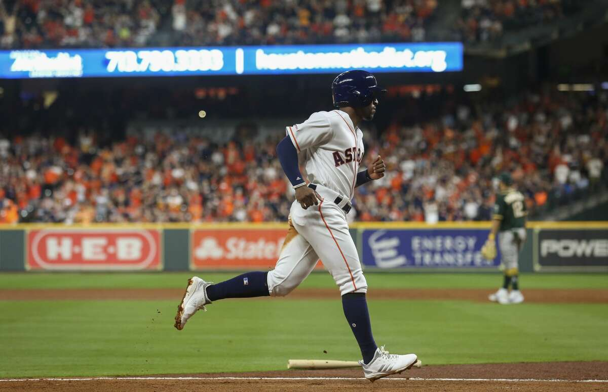 Houston Astros left fielder Tony Kemp (18) scores off third baseman Alex Bregman's (2) single against the Oakland Athletics during the third inning of an MLB game at Minute Maid Park Friday, April 5, 2019, in Houston.