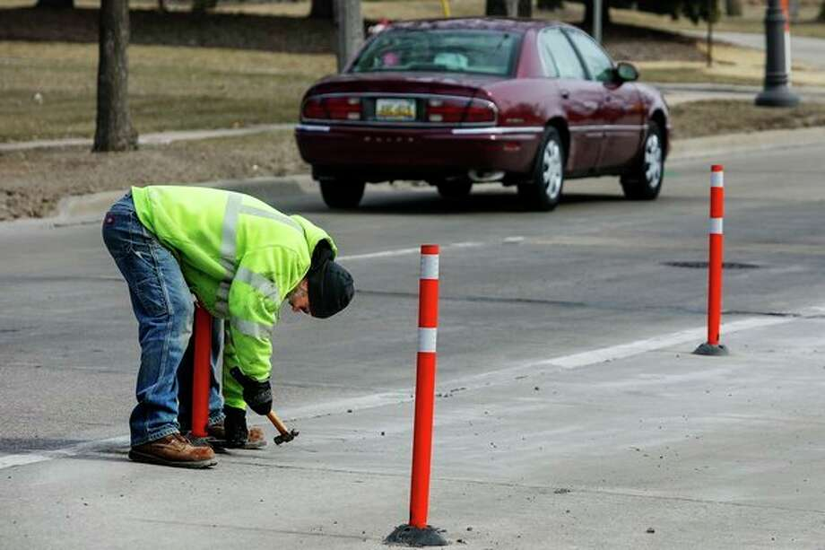 David Lees with the City of Midland Department of Public Works installs a traffic delineator post on Buttles Street Thursday afternoon in Midland. The posts keep drivers from using the far right lane, which has been closed off since March of 2018 during the imposition of a road diet. (Katy Kildee/kkildee@mdn.net)