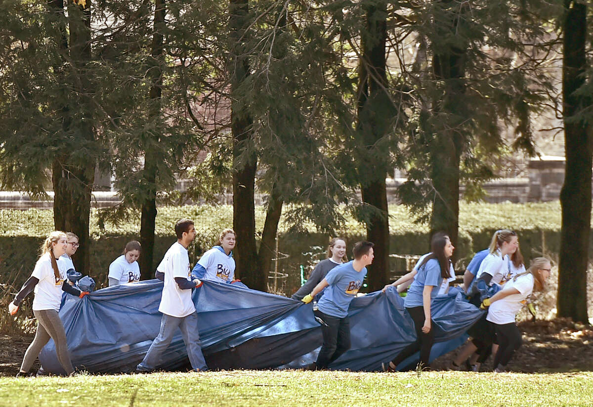 New Haven, Connecticut - Saturday, April 6, 2019: Quinnipiac University students pulling a tarp full of landscape debris at Edgerton Park Saturday are among the approximately 1500 Quinnipiac University Big Event honors program students participating Saturday in the 10th annual Big Event cleanup at 75 locations in greater New Haven area.