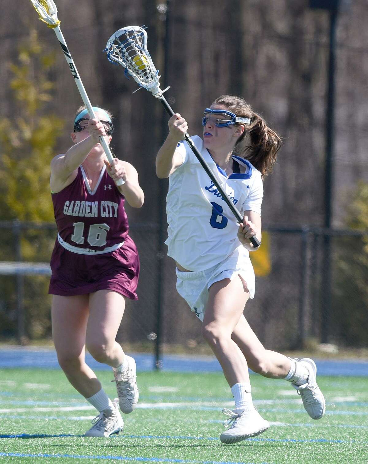 Darien's Katie Elders (6) drives to the net while Garden City's Caitlin Cook (16) defends during a girls lacrosse game at Darien High School on Saturday, April 6, 2019.