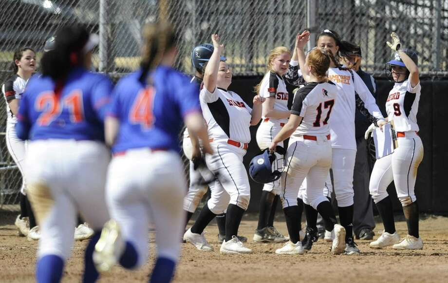 Stamford's Diana Magarian (17) celebrates with her teammates after driving in the winning run with a single in the 10th inning of the Black Knight's 7-6 victory over Danbury on Saturday in Stamford. Photo: Matthew Brown / Hearst Connecticut Media / Stamford Advocate