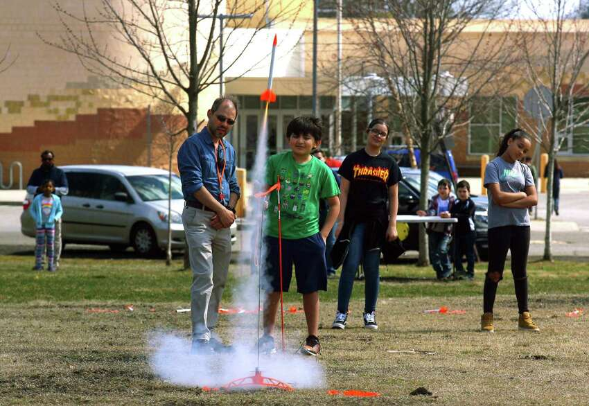 Instructor David Mestre and Jerson Bustillo, 10, watch as Jerson launches his rocket from Veterans Field during the Discovery Museum's annual Science Day in Bridgeport, Conn., on Saturday Apr. 6, 2019. As many as 1400 children got to take part in a variety of activities related to space research and exploration. Some of the highlights included a Live Science Demo, Astronaut Training, drone flights with Connecticut Wild Flyers and even a piece of moon rock on display. Science Day is made possible by a grant from the NASA Connecticut Space Grant Consortium.