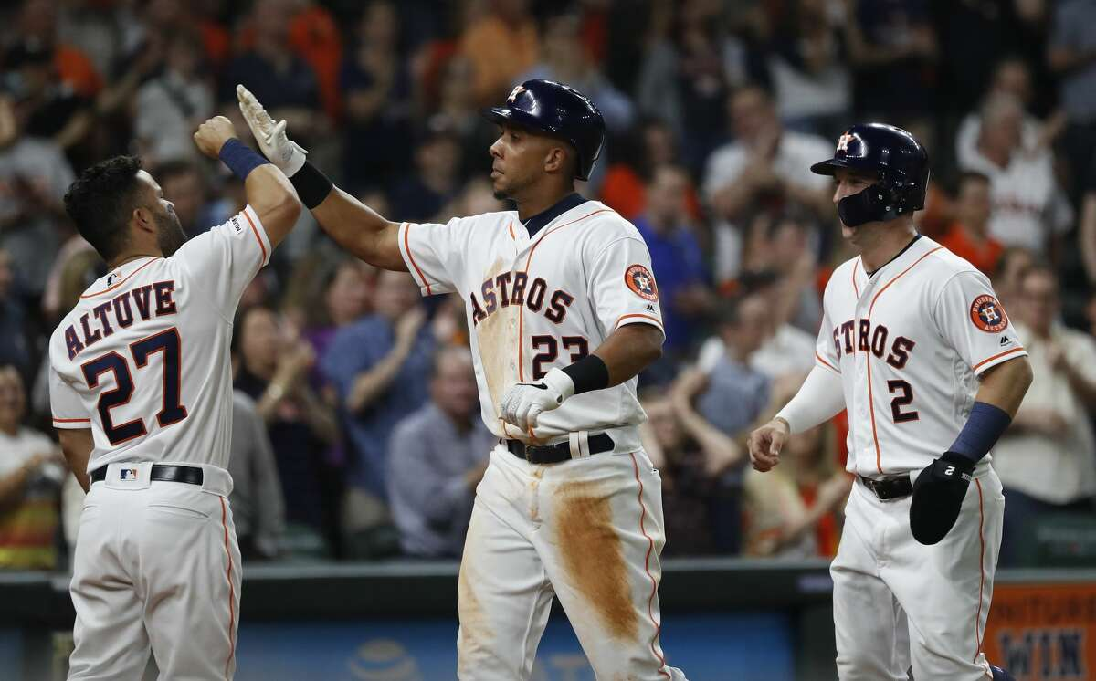Houston Astros left fielder Michael Brantley (23) celebrates his two-run home run with Jose Altuve (27) and Alex Bregman (2) during the fifth inning of an MLB at Minute Maid Park, Saturday, April 6, 2019, in Houston.