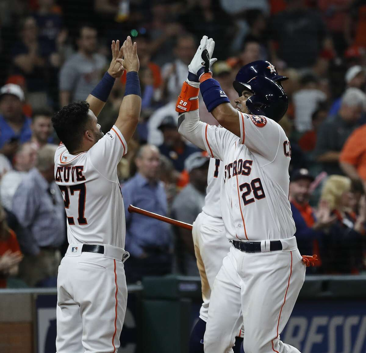 Houston Astros catcher Robinson Chirinos (28) celebrates with George Springer (4) and Jose Altuve (27) after hitting his home run during the sixth inning of an MLB at Minute Maid Park, Saturday, April 6, 2019, in Houston.