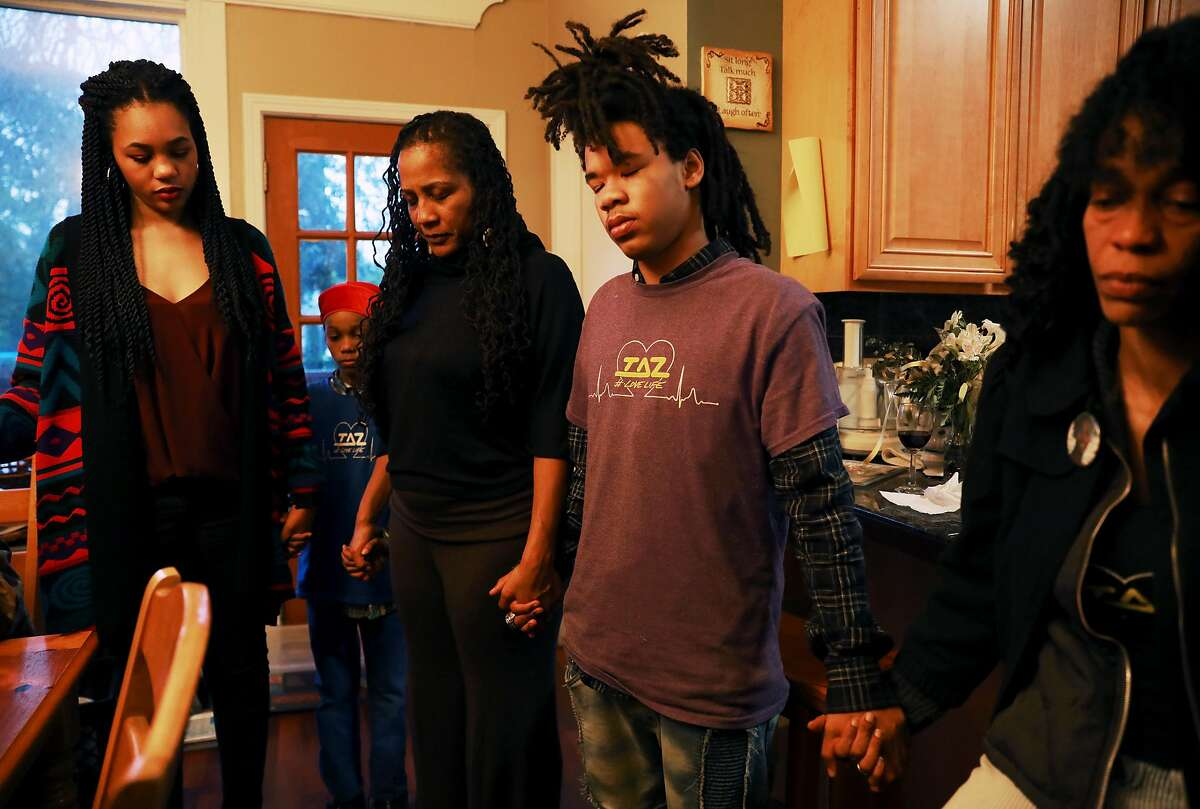 Shekhiynah Larks (left), Ishy-Me Hughes, Oakland councilwoman Lynette McElhaney, Amir Cornish, AudreyCandyCorn and others bow their heads in prayer as McElhaney holds a prayer service in her Oakland home to honor her slain son Victor in Oakland, Calif., on Friday, April 5, 2019. Victor McElhaney, 21, was fatally shot last month during an armed robbery attempt in Los Angeles.