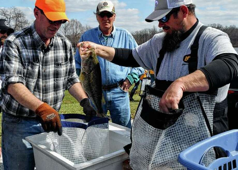 Richard Snodgrass (right) of Bluffs and Jacksonville rotarian David Fisher prepare a fish to be weighed Saturday during the Jacksonville High School Bass Fishing Team's first bass tournament on Lake Jacksonville. Photo: Samantha McDaniel-Ogletree | Journal-Courier