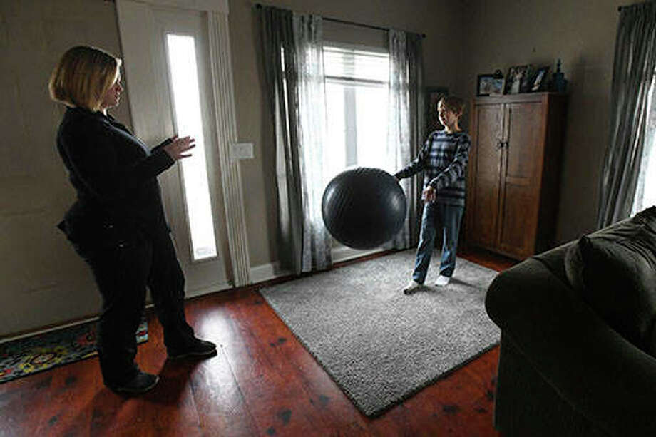 Isaiah Lundmark, 11, of Clifton does physical therapy at home with therapist Brooks Stenoish of Presence Home Care. Diagnosed with Lyme Disease in September 2017, Isaiah uses physical therapy to regain and maintain his strength. Photo: Tiffany Blanchette | The Daily Journal (AP)