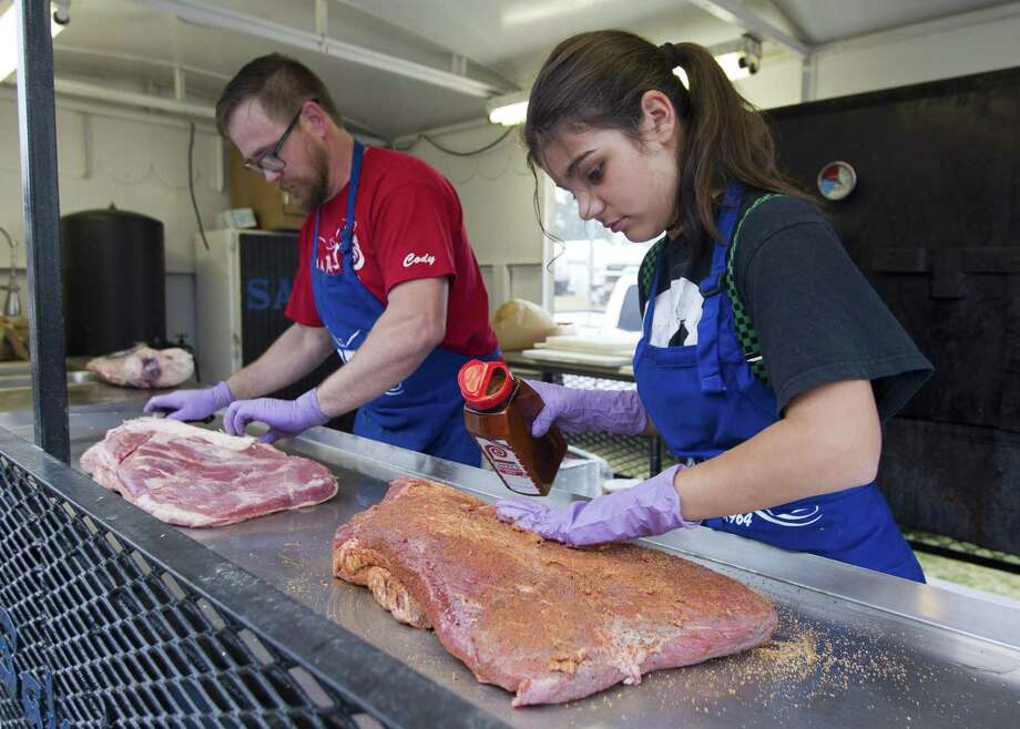 Cody Reese and his cousin Vivian Townsend prepare brisket as part of the Montgomery County Fair and Rodeo's annual barbecue contest, Friday, April 5, 2019, in Conroe. 148 teams compete for the top brisket, ribs, chicken and pulled pork. Photo: Jason Fochtman, Houston Chronicle / Staff Photographer / © 2019 Houston Chronicle