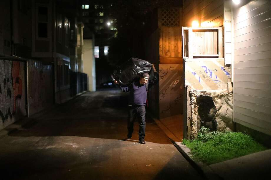 Jake Orta hauls a bag filled with discarded items out of an alley in San Francisco on Jan. 25, 2019.  A military veteran who fell into homelessness and now lives in government subsidized housing, Orta is a full-time trash picker, part of an underground economy in San Francisco of people who work the sidewalks in front of multi-million-dollar homes, rummaging for things they can sell. (Jim Wilson/The New York Times) Photo: Jim Wilson, NYT