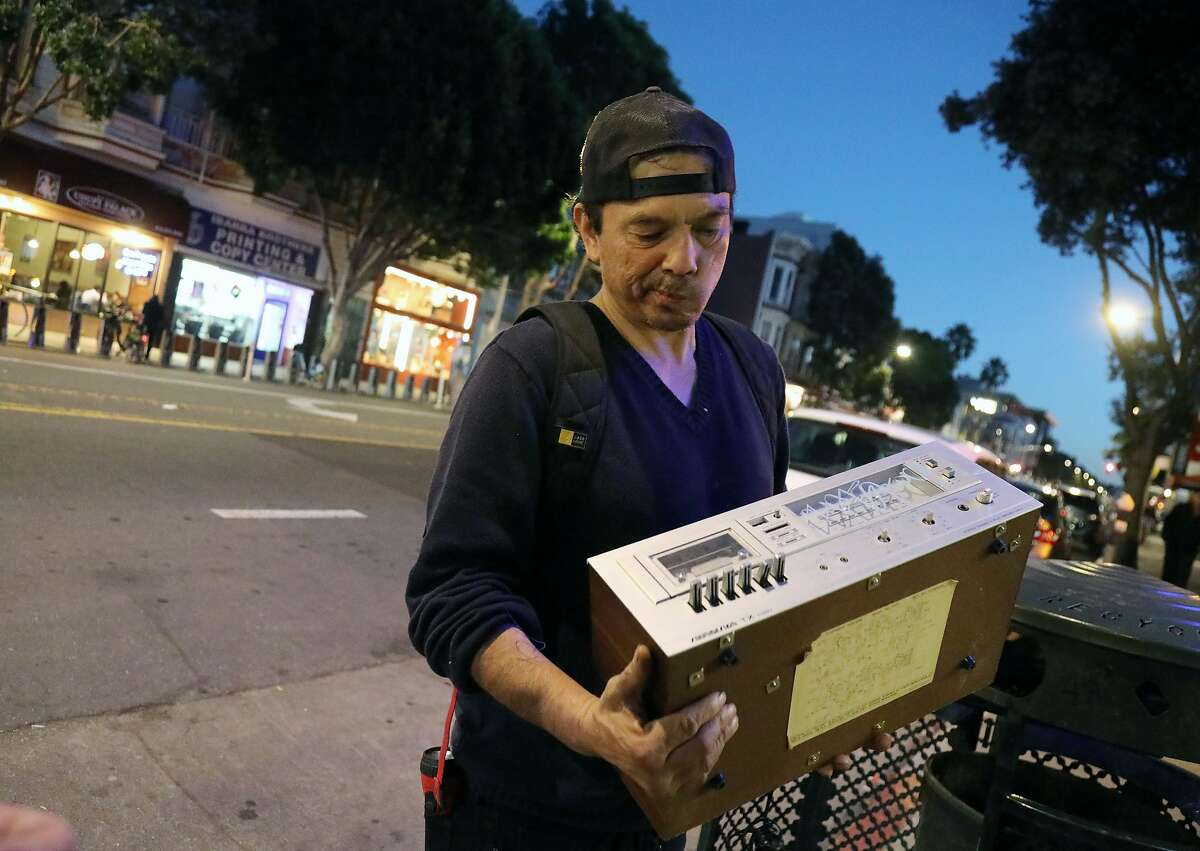 Jake Orta examines an old cassette tape deck that he found discarded on the street in San Francisco on Jan. 25, 2019. A military veteran who fell into homelessness and now lives in government subsidized housing, Orta is a full-time trash picker, part of an underground economy in San Francisco of people who work the sidewalks in front of multi-million-dollar homes, rummaging for things they can sell. (Jim Wilson/The New York Times)