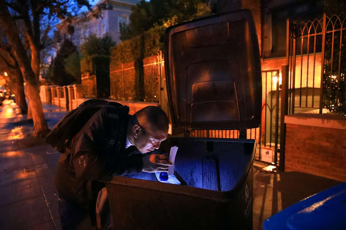 Jake Orta looks through a trash can outside of Mark Zuckerberg's home in San Francisco on April 3, 2019. A military veteran who fell into homelessness and now lives in government subsidized housing, Orta is a full-time trash picker, part of an underground economy in San Francisco of people who work the sidewalks in front of multi-million-dollar homes, rummaging for things they can sell. (Jim Wilson/The New York Times)