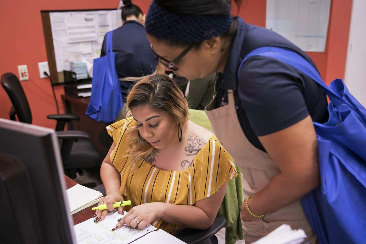 Esmerelda Garcia, center, helps with paperwork during morning deployment on Friday, April 5, 2019, at Maid Brigade, a residential cleaning service in Gulfton.