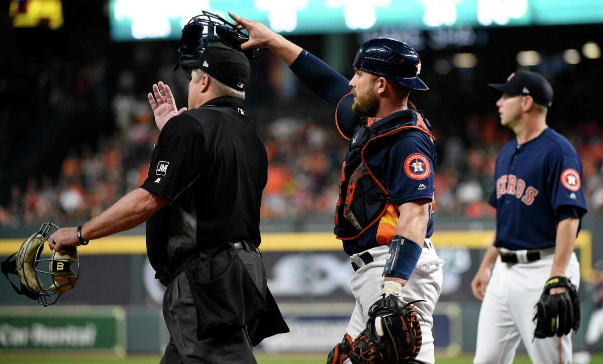 Houston Astros catcher Max Stassi, center, argues about an RBI-double by Oakland Athletics' Chad Pinder with home plate umpire Marvin Hudson, left, as Astros starting pitcher Brad Peacock, right, watches during the first inning of a baseball game, Sunday, April 7, 2019, in Houston. (AP Photo/Eric Christian Smith)