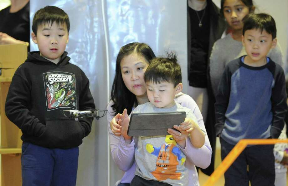 Greta Kim of Greenwich helps her son Chester, 3, fly a mini drone while his older brother Milo, 5, watches during an Innovation Experience at the Greenwich Library Saturday, April 6, 2019 in Greenwich, Connecticut. Several hundred visitors took part in seminars offered in robotics, drones, augmented and virtual reality, 3D printing and LED projects. Photo: Matthew Brown / Hearst Connecticut Media / Stamford Advocate