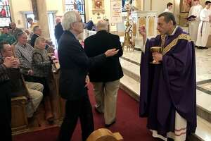 Bishop Frank Caggiano gives communion during a Mass of Hope, Healing, and Reconciliation for victims of clerical sexual abuse at St. Joseph Church in Danbury, Conn. on Sunday, April 7, 2019.
