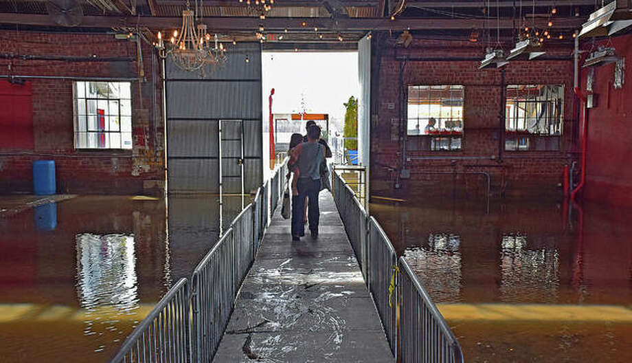 It was supposed to host the Motorcycle Swap Meet on Sunday, but the Loading Dock was full of flood waters that required a causeway to reach the restaurant and bar on the other side. Photo: David Blanchette | For The Telegraph