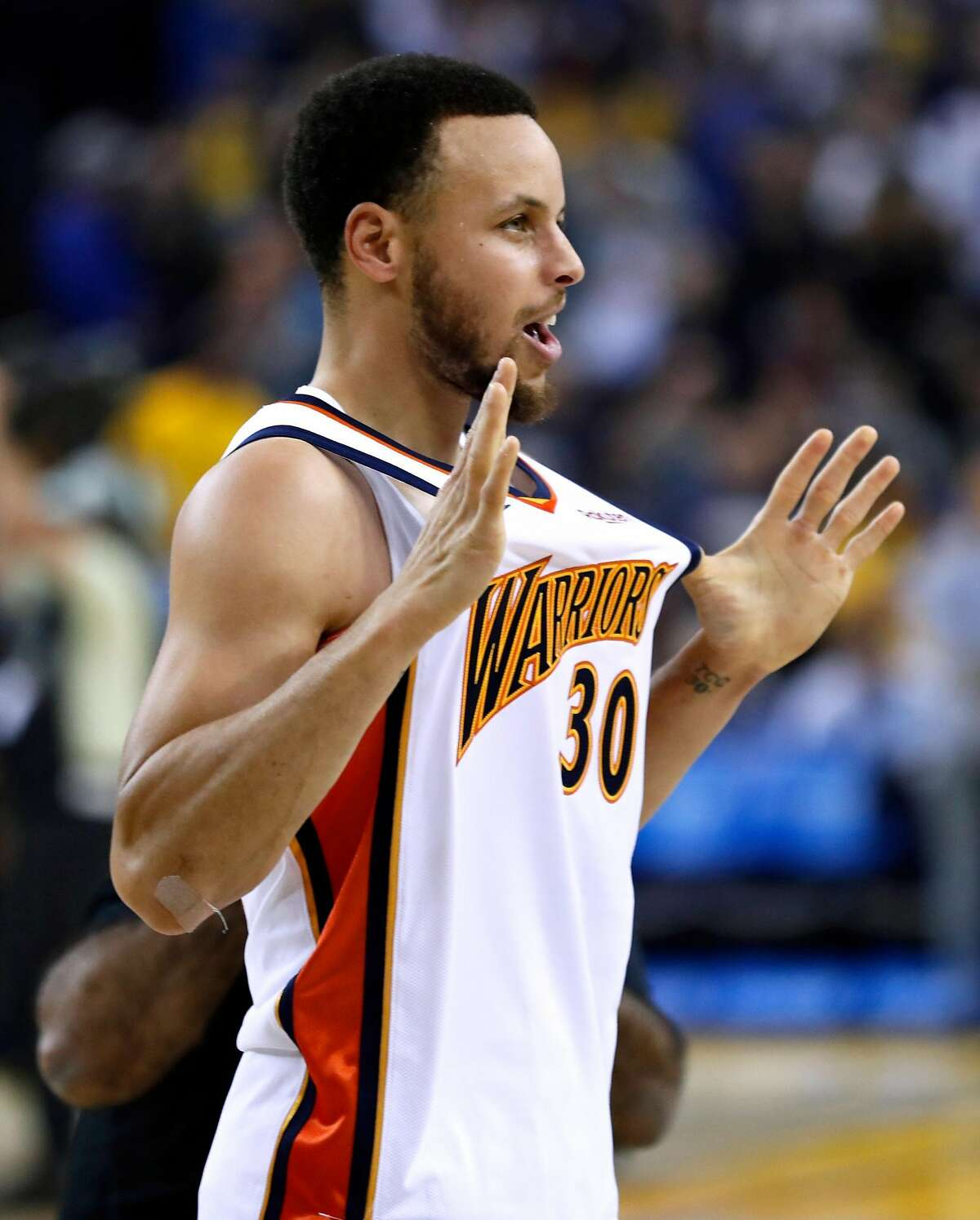 """Golden State Warriors' Stephen Curry shows off """"We Believe"""" era jersey before playing Los Angeles Clippers during NBA game at Oracle Arena in Oakland, Calif., on Sunday, April 7, 2019."""