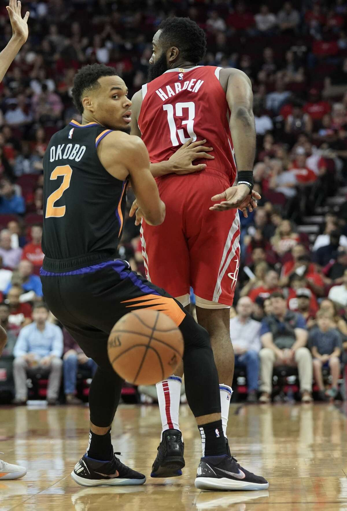 Houston Rockets guard James Harden (13) dishes the ball of behind him around Phoenix Suns guard Elie Okobo (2) at the Toyota Center on Sunday, April 7, 2019. Rockets won the game 149-113.