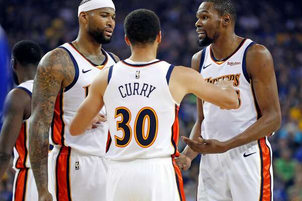 Golden State Warriors' Kevin Durant and Stephen Curry give direction to DeMarcus Cousins in 1st quarter while playing Los Angeles Clippers during NBA game at Oracle Arena in Oakland, Calif., on Sunday, April 7, 2019.