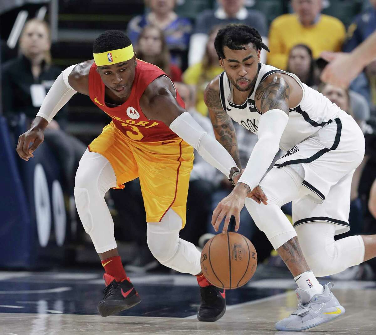 Indiana Pacers' Aaron Holiday (3) and Brooklyn Nets' D'Angelo Russell (1) go for a loose ball during the first half of an NBA basketball game Sunday, April 7, 2019, in Indianapolis. (AP Photo/Darron Cummings)