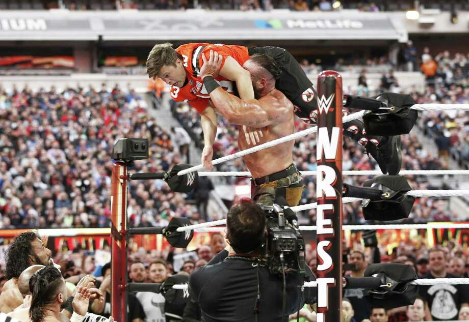 EAST RUTHERFORD, NEW JERSEY - APRIL 07: Braun Strowman tosses Colin Jost out of the ring during SNL's Michael Che and Colin Jost at WWE WrestleMania at Met Life Stadium on April 07, 2019 in East Rutherford, New Jersey. (Photo by Brian Ach/Getty Images for WWE) Photo: Brian Ach / Getty Images For WWE / 2019 Getty Images