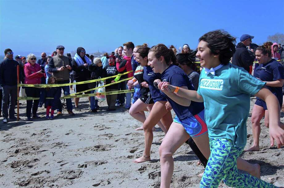 Teammates hold hands as they prepare for the cold water at the Special Olympics' Penguin Plunge at Jennings Beach on Saturday, April 6, 2019, in Fairfield, Conn. Photo: Jarret Liotta / For Hearst Connecticut Media / Fairfield Citizen News Freelance