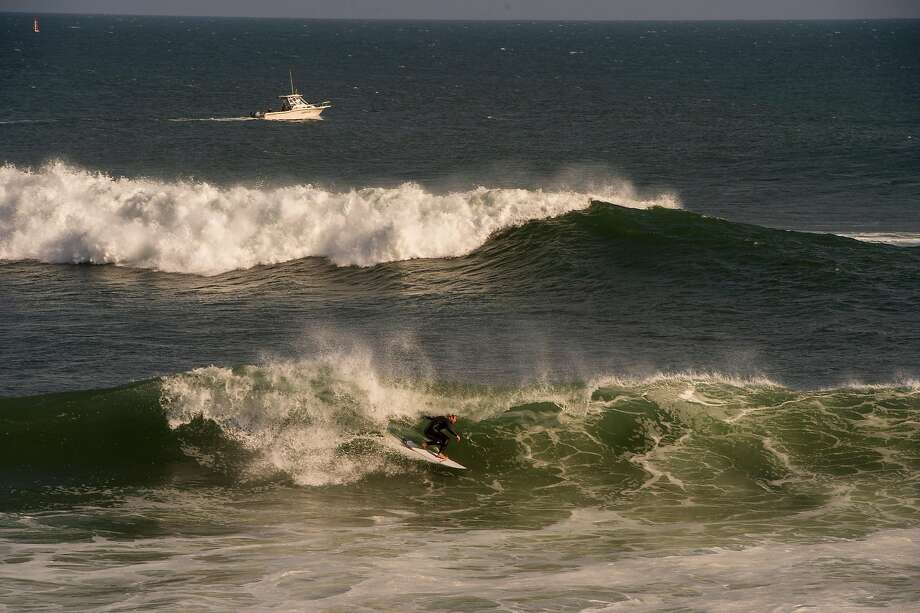 A surfer catches a wave at Steamer Lane in Santa Cruz, Calif. Photo: Nic Coury / Special To The Chronicle