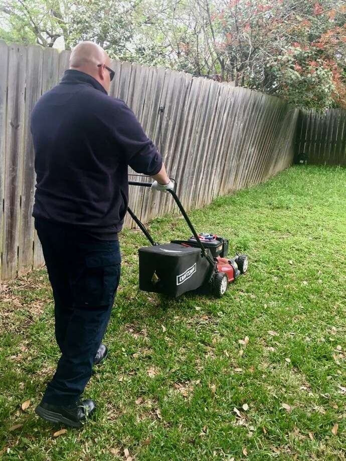 Converse firefighter Delmiro Soliz takes time out to mow the yard of a Converse resident who was taken to the hospital by Converse EMTs after the resident was injured while he was working in his yard. Photo: Courtesy Photo /