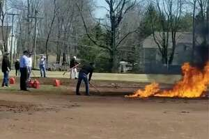 Unidentified people tend to a blaze on Ridgefield's Ciuccoli Field on Saturday afternoon April 8, 2019. before Ridgefield High School was set to play Amity in a baseball game. Police are still investigating the reason and responsible parties involved, which the town says will cost an estimated $50,000 to clean up. The game was moved to Amity's field in Woodbridge by the afternoon. Ridgefield won, 5-4.