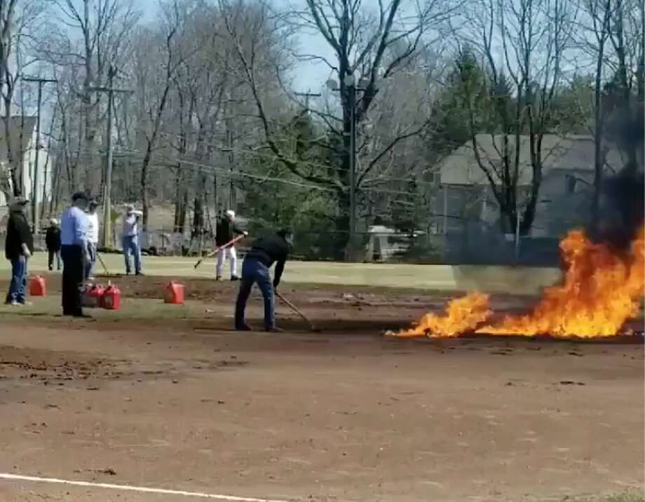 Unidentified people tend to a blaze on Ridgefield's Ciuccoli Field on Saturday afternoon April 8, 2019. before Ridgefield High School was set to play Amity in a baseball game. Police are still investigating the reason and responsible parties involved, which the town says will cost an estimated $50,000 to clean up. The game was moved to Amity's field in Woodbridge by the afternoon. Ridgefield won, 5-4. Photo: @AmityNorton On Twitter