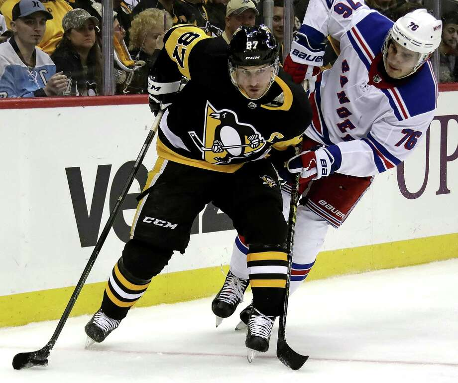 FILE - In this April 6, 2019 file photo Pittsburgh Penguins' Sidney Crosby (87) holds off New York Rangers' Brady Skjei (76) as he works the puck in the offensive zone during during the second period of an NHL hockey game in Pittsburgh. The Penguins are headed to the NHL playoffs for the 13th straight year thanks in large part to Crosby's ability to help prevent goals as easily as he scores them, making him a dark-horse candidate for the Selke Trophy, the award given annually to the top defensive forward in the NHL. (AP Photo/Gene J. Puskar, File) Photo: Gene J. Puskar / Associated Press / Copyright 2019 The Associated Press. All rights reserved