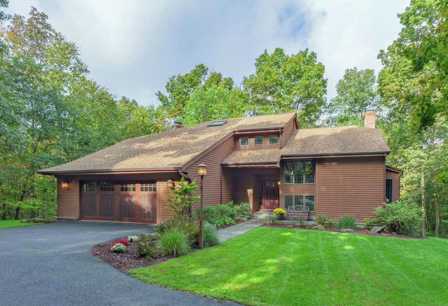 The Energy Star-rated contemporary house at 76 Spectacle Lane sits on a 2.83-acre level and sloping property in a secluded woodland setting.