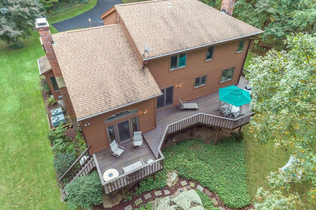 This 3,133-square-foot house is located down a very long driveway on a level and sloping property of almost three acres near the border of Ridgefield.