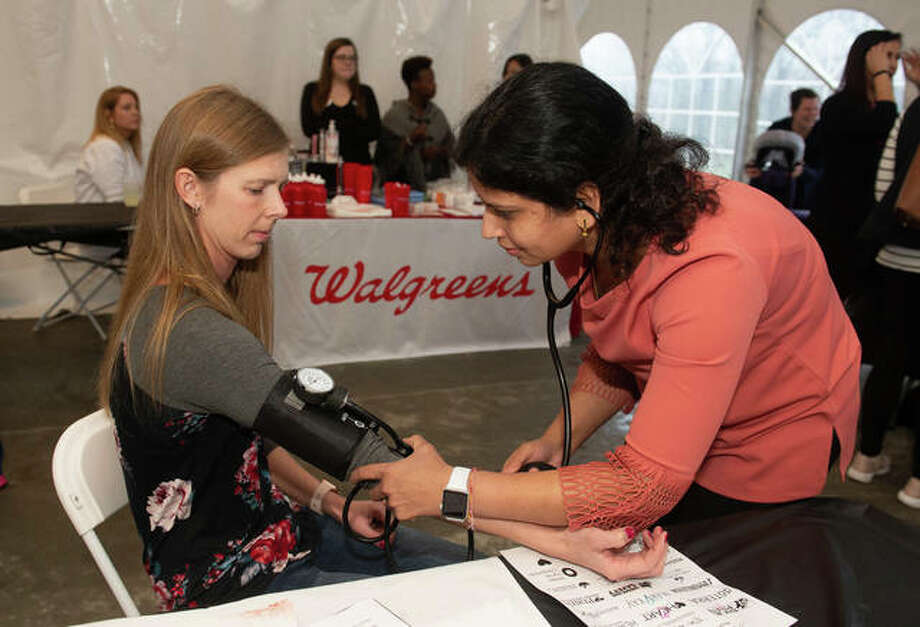 Third-year School of Pharmacy student Smita Rausaria checks the blood pressure of event participant Sue Slimack, of Belleville. Photo: For The Intelligencer