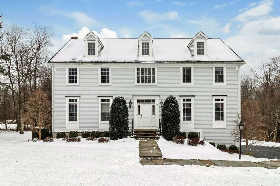 The gray colonial house with white trim at 42 Vista Drive sits on a level and very gently sloping property of just over three acres on a quiet cul-de-sac. Photo: PlanOmatic / © 2019 PlanOmatic