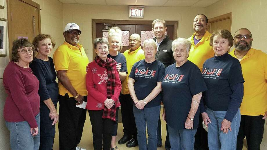 Members of the Colbert Athletic Association (in yellow shirts) and volunteers at the First United Methodist Church in Dayton gathered for a photo following the CAA donation to needy families last December. Photo: Submitted