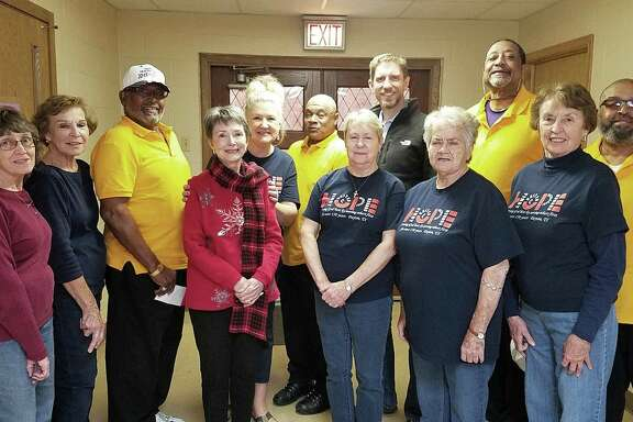 Members of the Colbert Athletic Association (in yellow shirts) and volunteers at the First United Methodist Church in Dayton gathered for a photo following the CAA donation to needy families last December.