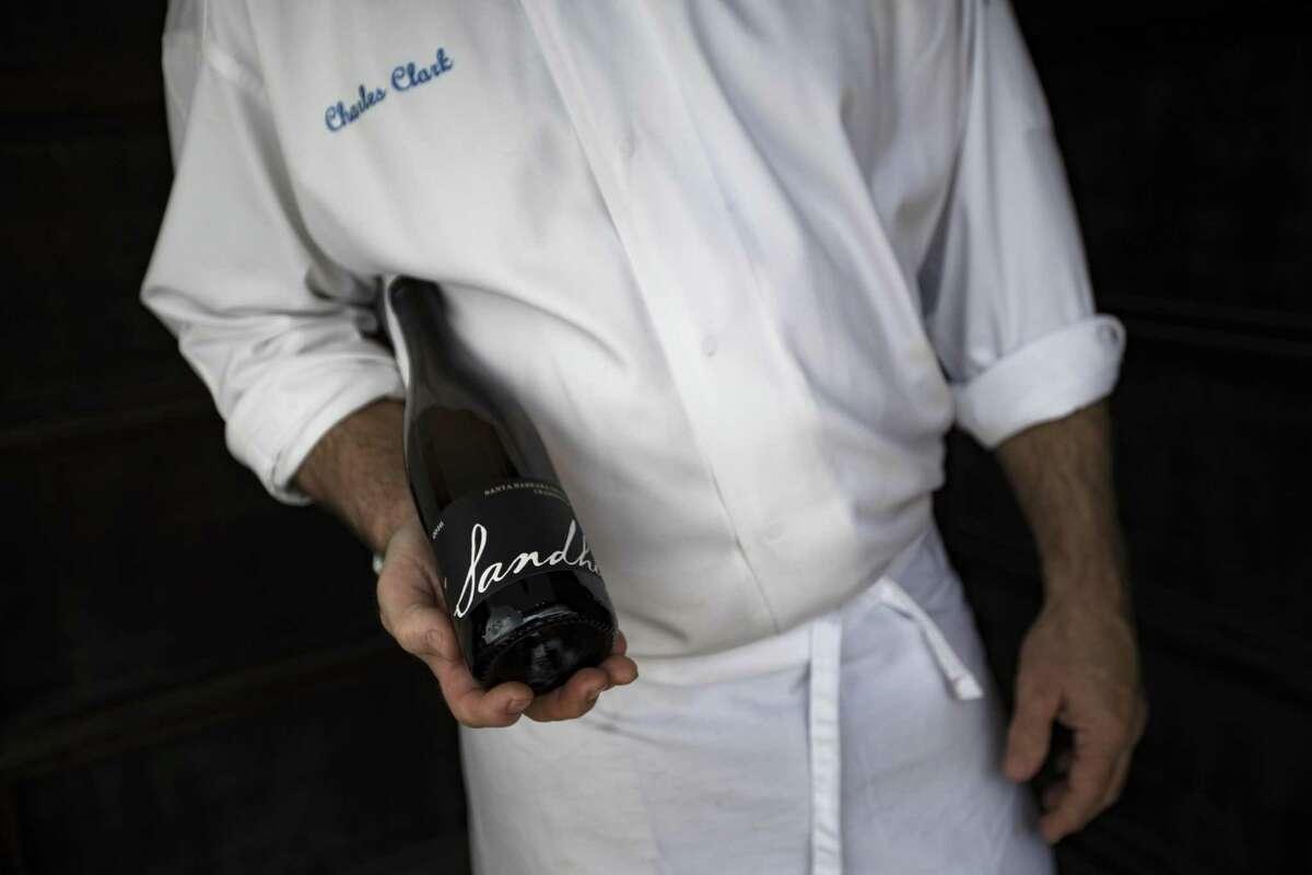 Ibiza chef-owner Charles Clark holds a bottle of 2016 Sandhi Santa Barbara Chardonnay