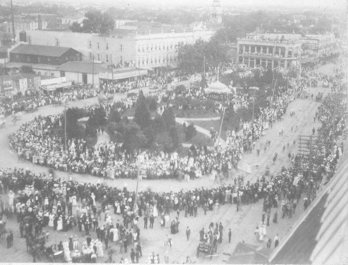 Looking southeast from Maverick Bank Building toward Alamo Plaza during the Battle of Flowers Parade c. 1898. Steeple of St. Joseph's Church under construction in distance.