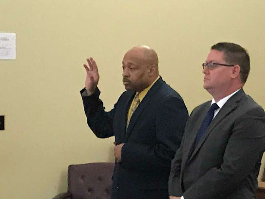 Retired Troy Detective Aaron Collington raises his hand as he appears with his attorney Josepha Ahearn Monday April 8, 2019 to plead guilty in Rensselaer County Court.