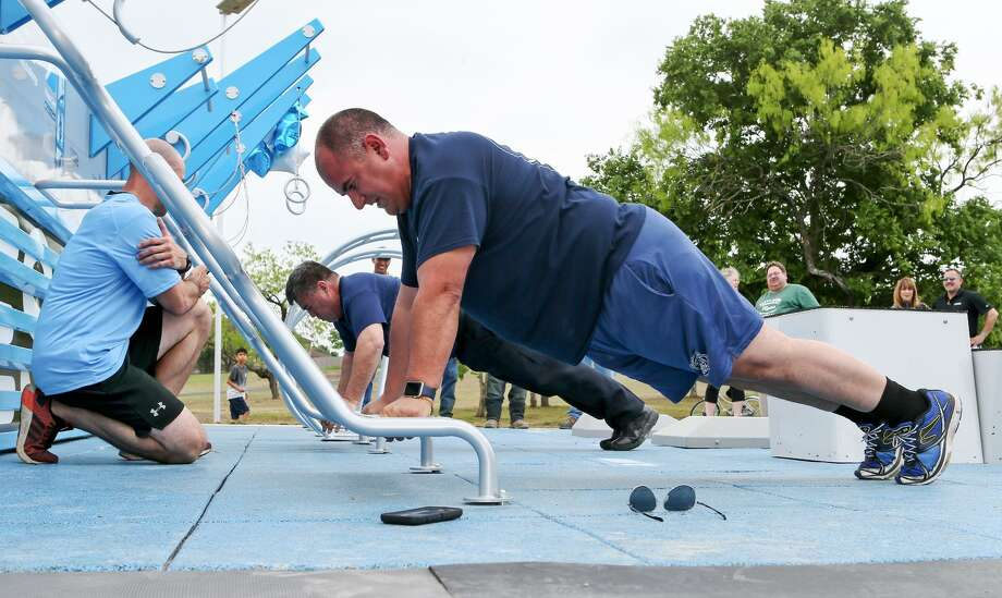 Converse fire chief Luis Valdez, front, and police chief Fidel Villegas compete in a push up challenge during the Converse Fitness Court Launch Party at the new outdoor gym in Converse City Park on Friday, April 5, 2019. The event featured an opening ceremony, head-to-head fitness challenge, and free boot camp workouts. Photo: Marvin Pfeiffer /Northeast Herald / Express-News 2019