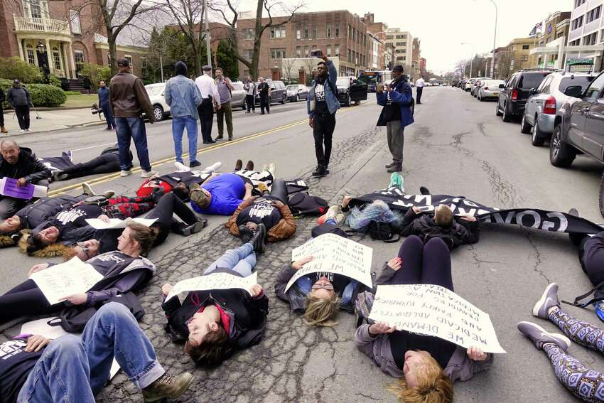 Protestors, representing those who have died from an overdose, lay down to block Washington Ave. outside the Medicaid Office on Monday, April 8, 2019, in Albany, N.Y. Members of Vocal-NY, End Overdoes New York, and Truth Pharm were calling for universal access to medication-assisted treatment (MAT) to end the overdose crisis. The protestors were also highlighting the critical and persistent problems with Medicaid that hinder MAT access. (Paul Buckowski/Times Union)