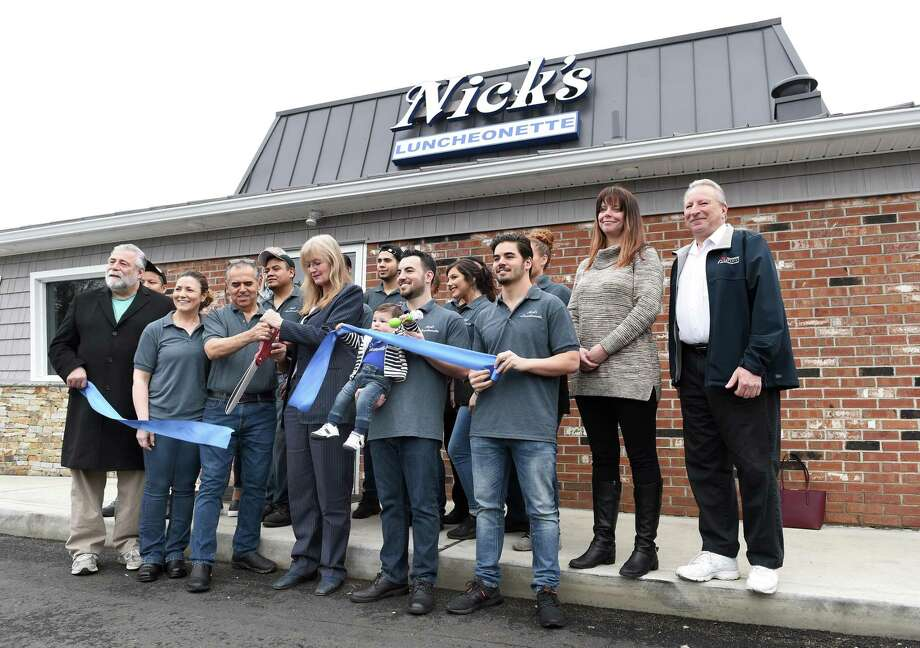 Nick Milas, owner of Nick's Luncheonette, third from left, front, and West Haven Mayor Nancy Rossi cut the ribbon for the relocated restaurant on Saw Mill Road April 8, 2019. Photo: Arnold Gold / Hearst Connecticut Media / New Haven Register