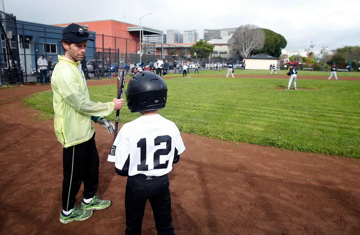 Jude Brennan (left) coaches Liam Reynolds during the Stratford Fire Lions youth baseball league game against the Commodore Sloat Seals at Victoria Manalo Draves Park on Folsom Street in San Francisco, Calif. on Saturday, April 6, 2019. Neighbors are concerned that a planned seven story residential project constructed at Folsom and Russ streets would create shadows on the park.
