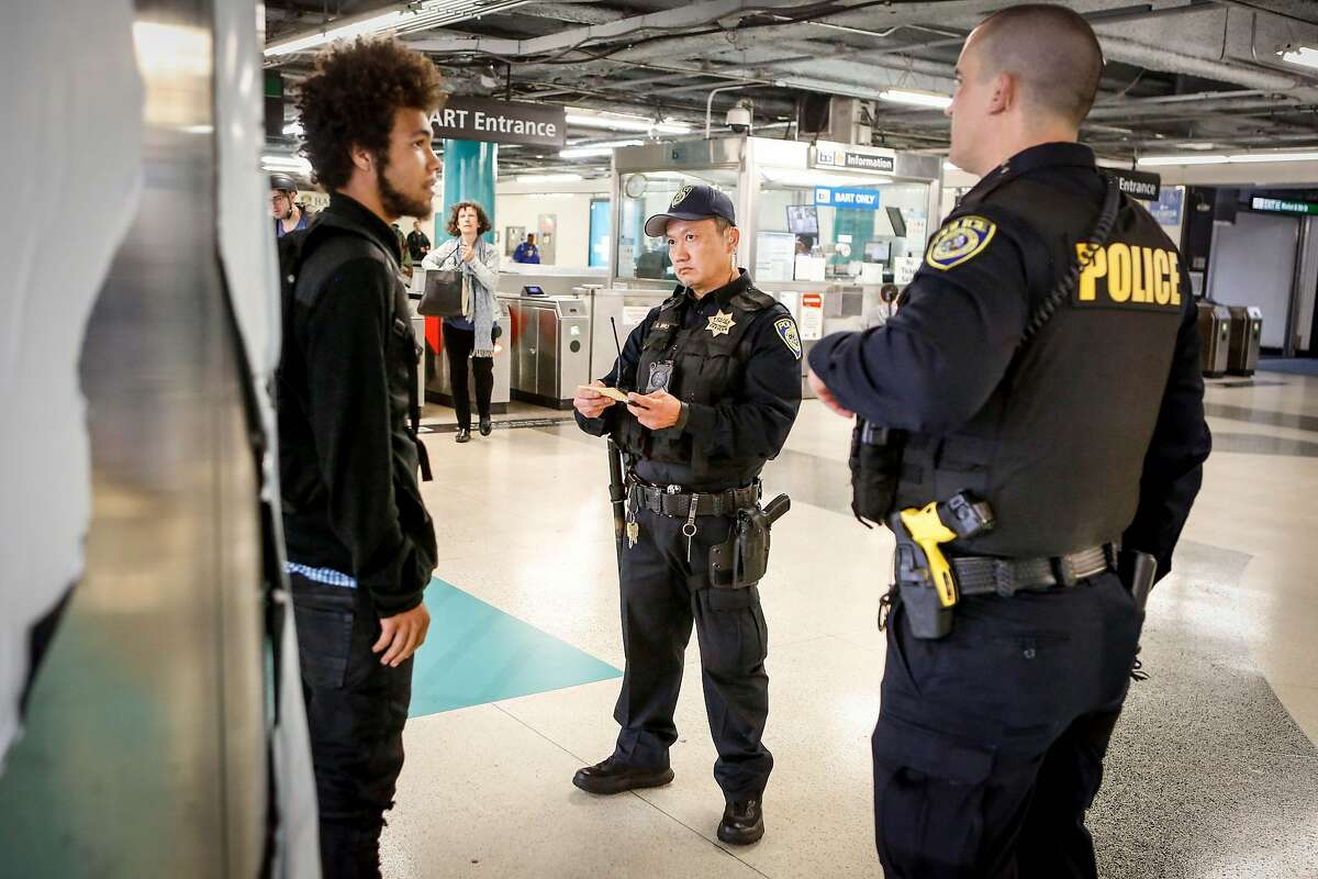 Police officers (L to R) S. Nho and M. Campbell take Jordyn Christo's information and issue him a warning at Powell Station BART entrance after Christo was caught jumping the fare gate on Monday, April 8, 2019 in San Francisco, Calif. Police officers are stationed at downtown stations as BART's large-scale fare evasion enforcement action.