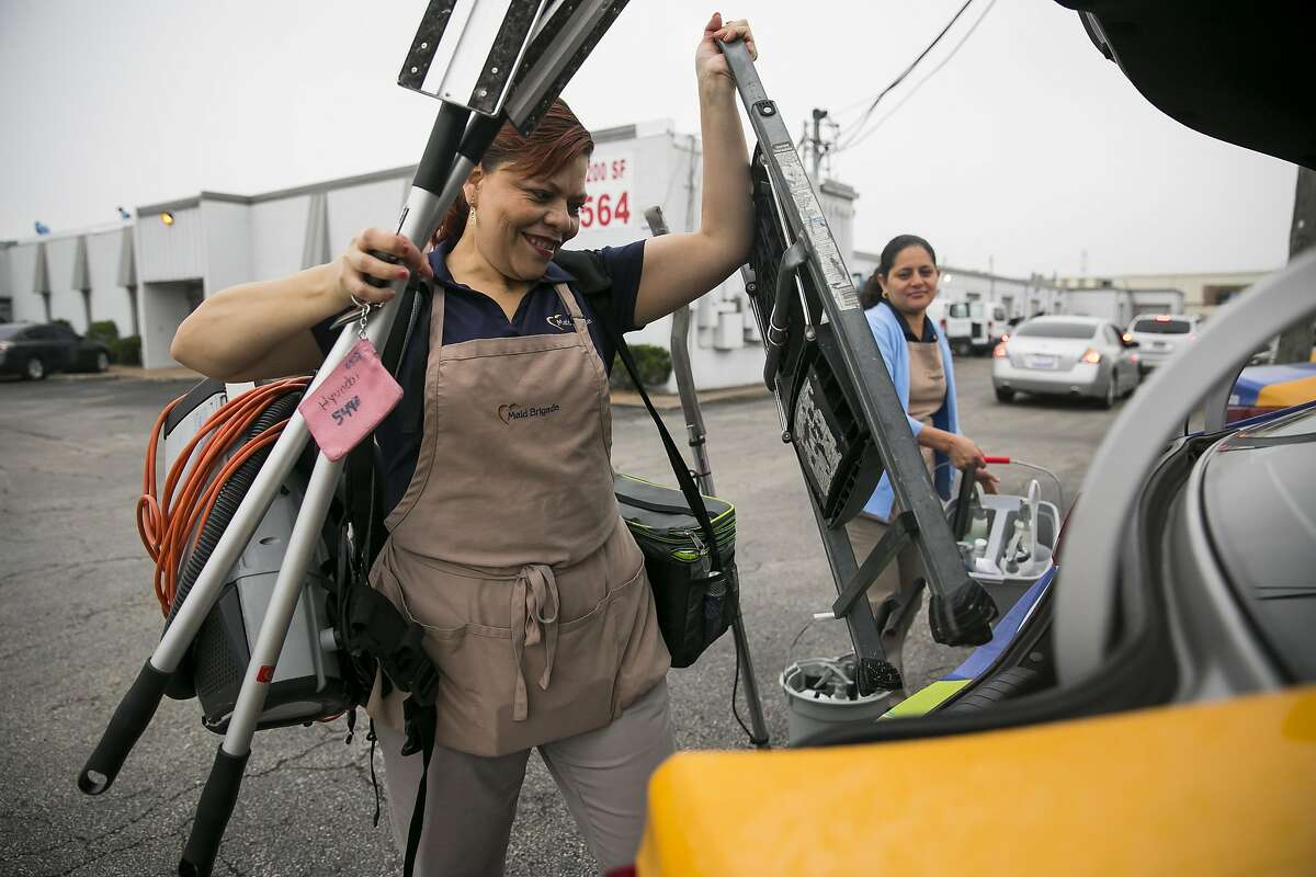 Adis Diaz loads cleaning supplies into a company car during morning deployment on Friday, April 5, 2019, at Maid Brigade, a residential cleaning service in Gulfton.