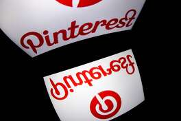 """(FILES) In this file photo taken on January 2, 2014 the logo of mobile app """"Pinterest"""" is displayed on a tablet in Paris. - Pinterest said April 8, 2019 it would raise up to $1.5 billion in its stock offering, setting a price range that trims the value of the online visual discovery startup. San Francisco-based Pinterest's price range of $15 to $17 a share would give it an estimated valuation of some $11 billion, below the $12 billion in its most recent private funding round. (Photo by Lionel BONAVENTURE / AFP)LIONEL BONAVENTURE/AFP/Getty Images"""